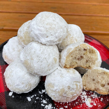 Golden shortbread cookie balls with chopped pecans rolled in white powdered sugar on a black and red checkered plate