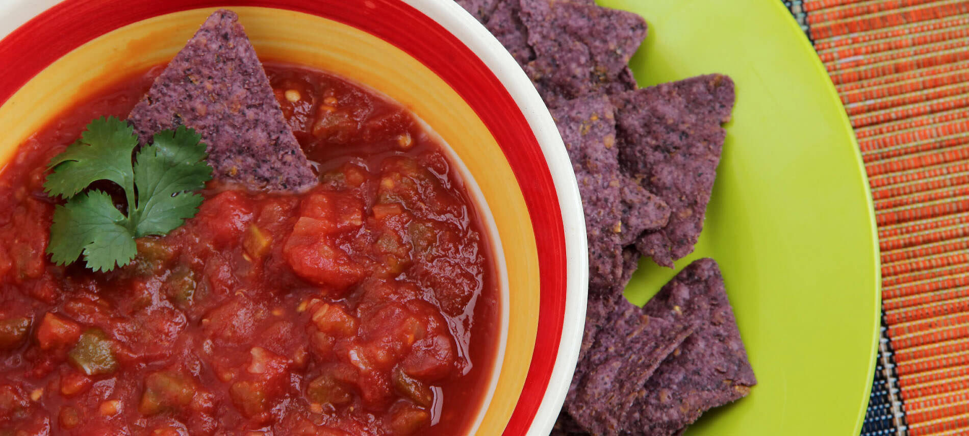 red salsa in a colorful bowl with purple tortilla chips on a green plate
