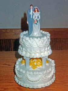 Two layer wedding cake with white decorated frosting and yellow roses with wedding couple on top