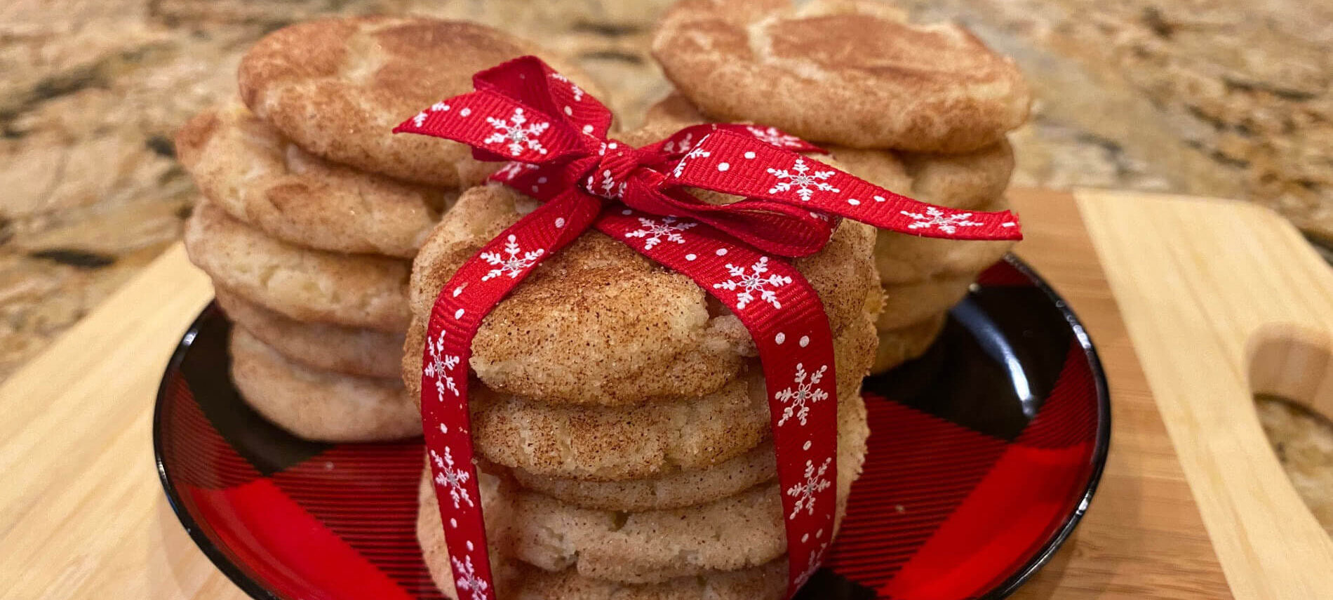 Golden round cookies coated with cinnamon and sugar, stacked and wrapped witjh a red and white snowflake ribbon