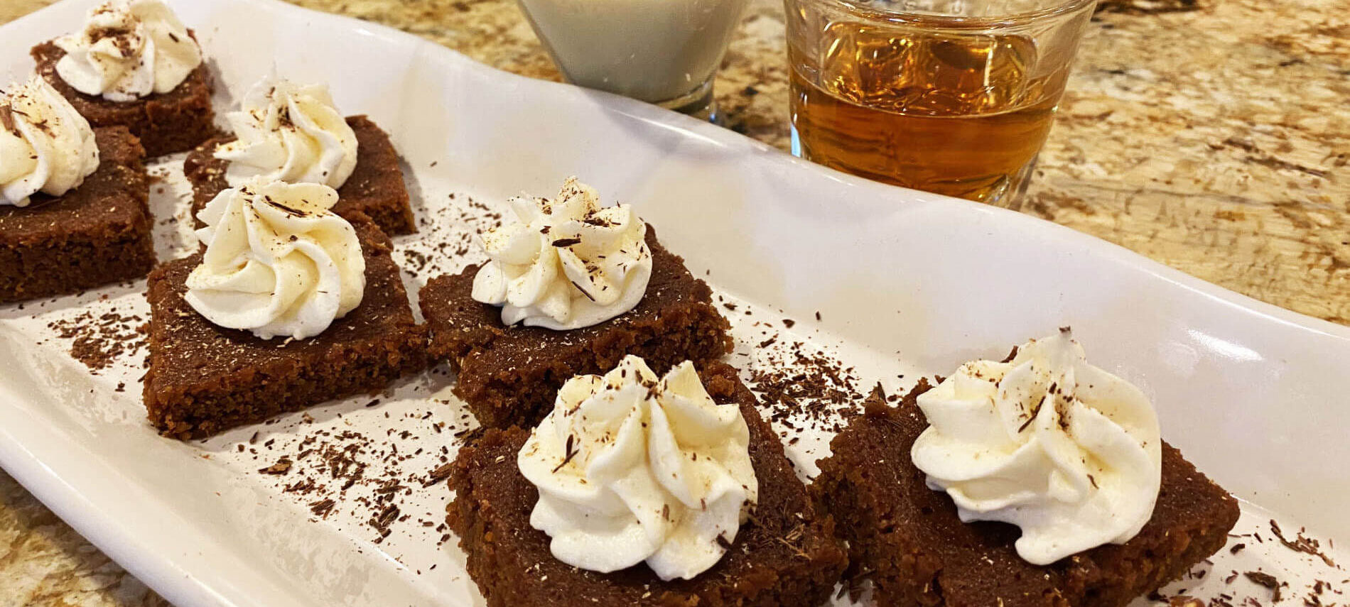 white plate with square brown brownies topped with white whipped cream and sprinkled with shaved chocolate, and glasses of white eggnog and golden bourbon
