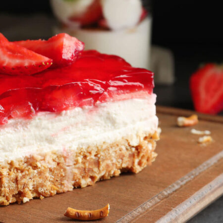 layered strawberry dessert with a pretzel crumb crust, cream filling, and red strawberry jello toppiing