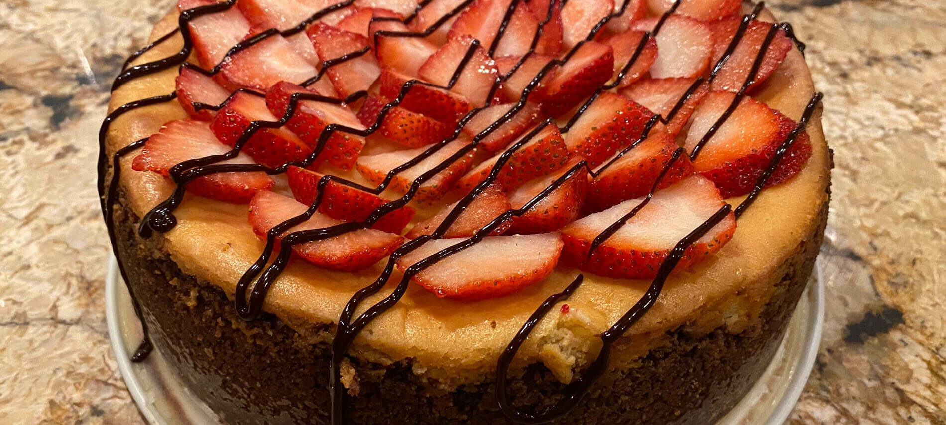 Creamy Champagne Cheesecake topped with red strawberry slices and drizzled with chocolate on a chocolate cookie crumb crust