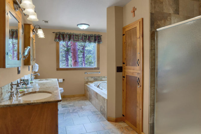 Large bathroom with double sinks, granite countertops, jetted tub for two, double sided shower, and window with mountain views