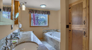 Bathroom with granite countertops, large jetted bathtub and large picture window with mountain views