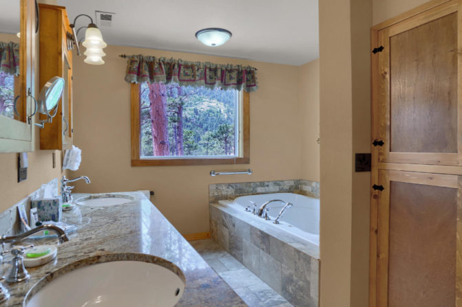 Bathroom with jetted tub for two, double sinks with granit countertop, and window with mountain views