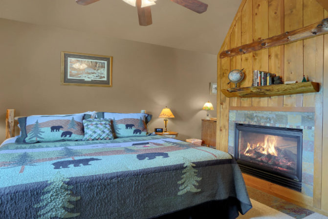 King bed with gas fireplace and wood mantle