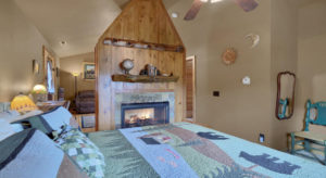 king bed with blue, green and black quilt with trees and bears, gas fireplace with fire, and wood mantle