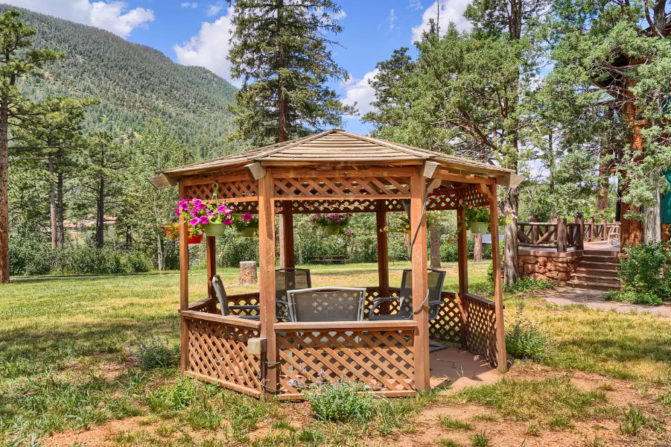Outdoor wood gazebo with trees and views of the mountains, and a portion of the outdoor terrace