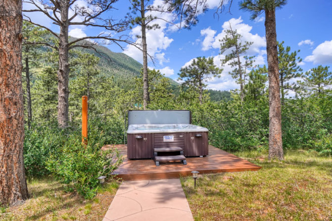 Large outdoor hot tub with deck and pathway amongst trees with views of the mountains