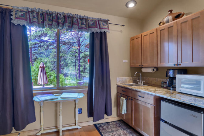 Cascade Luxury Suite has a private entrance, a sitting area with fireplace, Cable TV/DVD player, kitchenette, dining table, bathroom with jetted tub & double sided shower, king bed, Cable TV/DVD player, private outdoor hot tub, and mountain views.