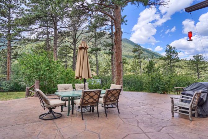 Outdoor patio with table, chairs and umbrella with mountain views