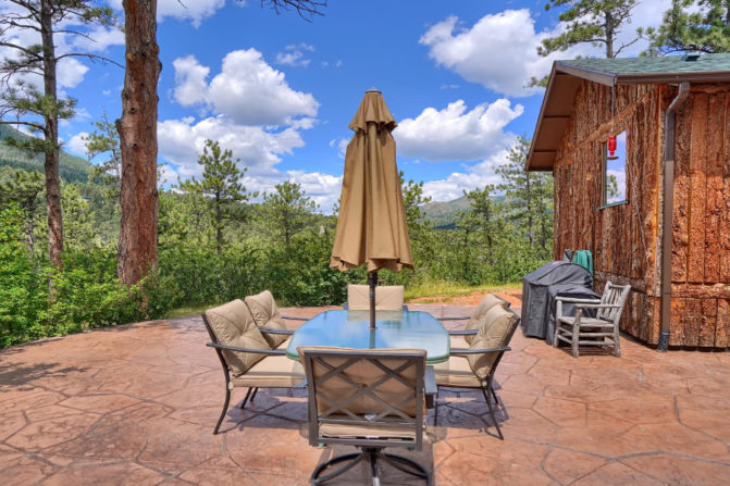 Outdoor patio with table, chairs, umbrella, BBQ, and views of the mountain and part of the Cascade Suite