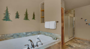 Large jetted bathtub with tan walls and green trees on the wall, and a large shower on the other side of the weall