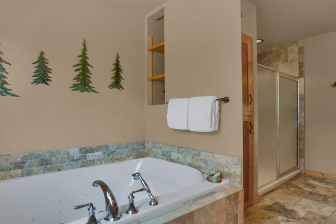 Large jetted tub for two with pine tree wall decor, and large walk in shower