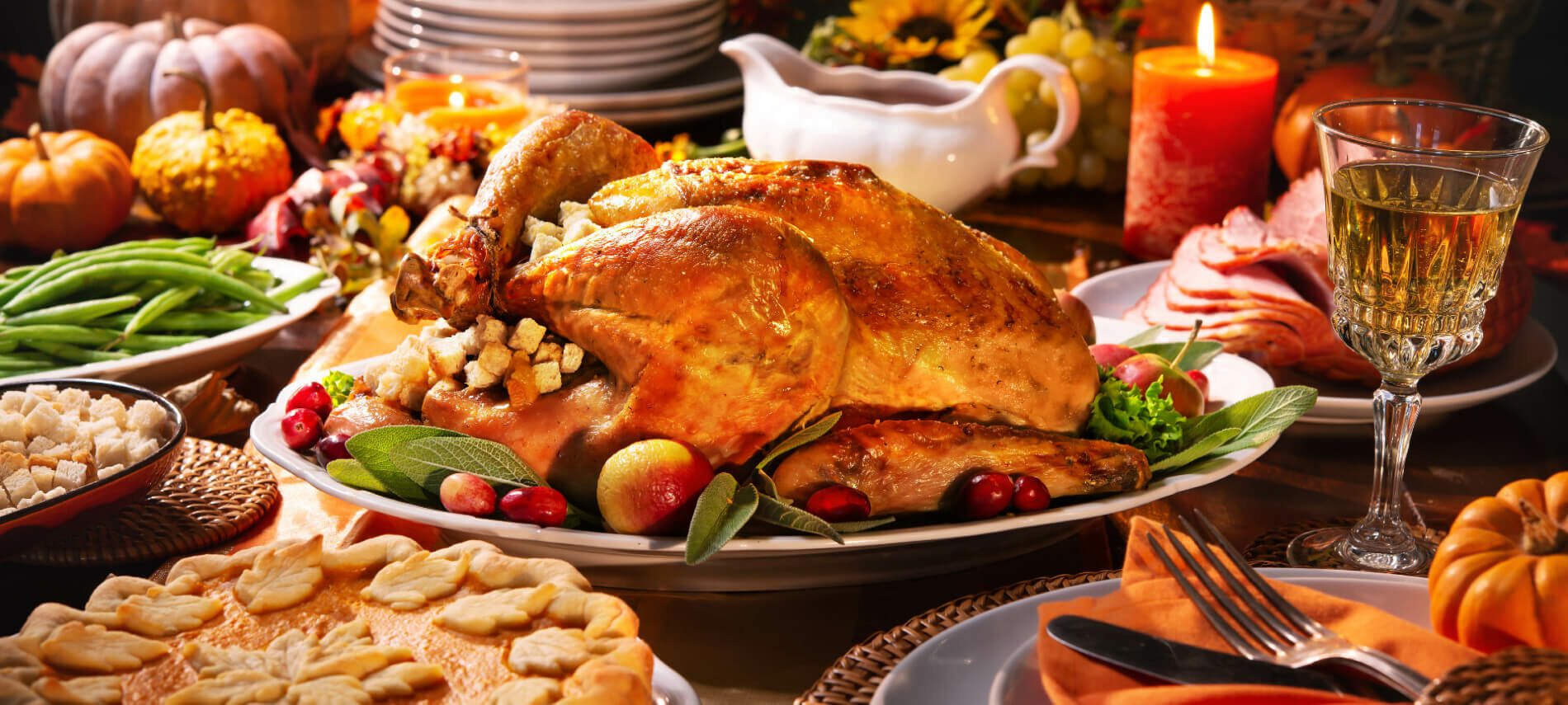Thanksgiving dinner with turkey, gravy, potatoes, pumpkin pie, white dishes and yellow sunflowers