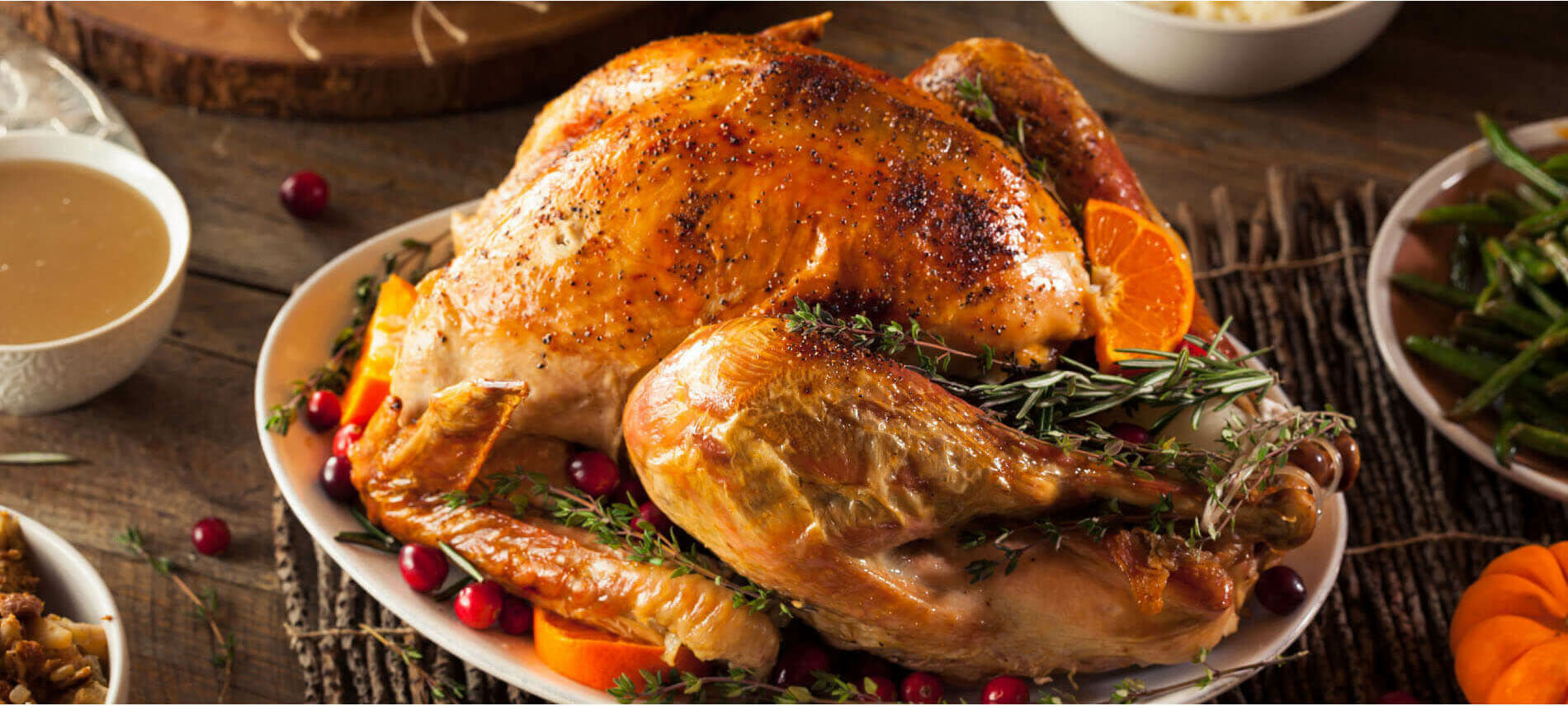 Golden roasted turkey with red cranberries, green herbs, brown gravy, green beans, and orange carrots