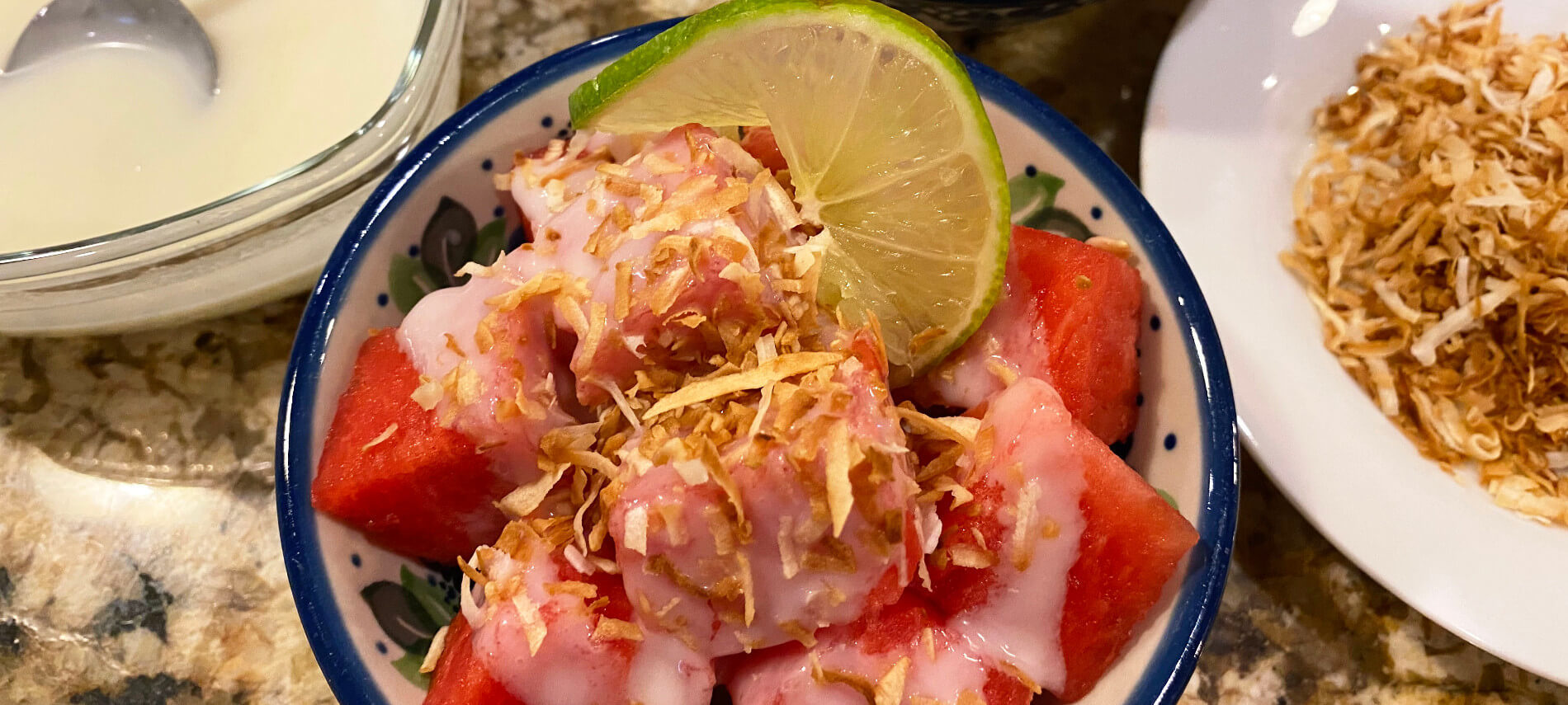 cubes of watermelon with a white coconut cream and golden brown coconut pieces, and a slice of lime