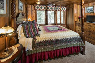 wood panelled bedroom with large bed covered in burgundy, cream and cream quilt against tri window to the outside with matching window treatment