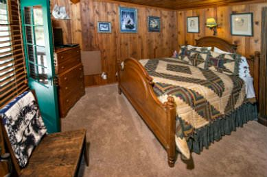 wood panelled bedroom with beige wall to wall carpeting with large wood fram bed covered with green and cream quilt with large stripe and geometric center design