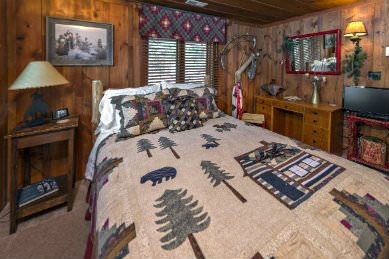 wood panelled bedroom with large bed covered in cream colored quilt with pine trees, bear and log cabin against double window with matching window treatment