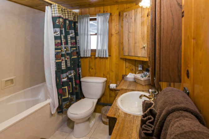 wood pannelled bathroom with tub and shower with rustic green, blue and checked shower curtain, wood topped vanity and brown towels