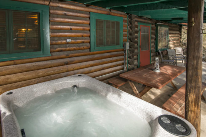 hot tub on deck outside log cabin with forest green trim and picknic table next to hot tub