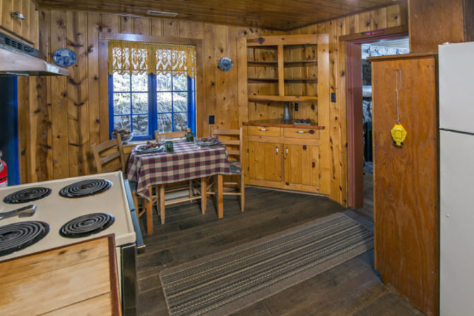 knotty pine wood panelled kitch with white appliances, neutral rug over darker hardwood on floor and table set for three with plaid linen and vibrant blue window trim and panes with gold lace valance