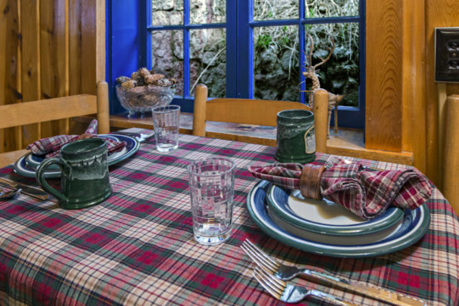 table set for three with red, gray and cream plaid table linen with matching napkins, blue, white and green pottery table setting in front of vibrant blue painted trim and window panes