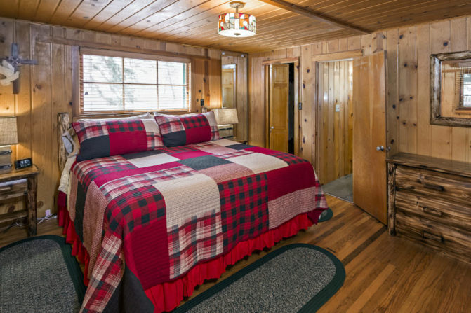 wood panelled bedroom with large window over king size bed covered with red, gray and cream colored patchwork quilt