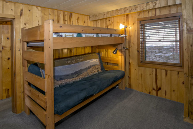 light wood paneleled room with rustic wood bunk beds and window with blinds