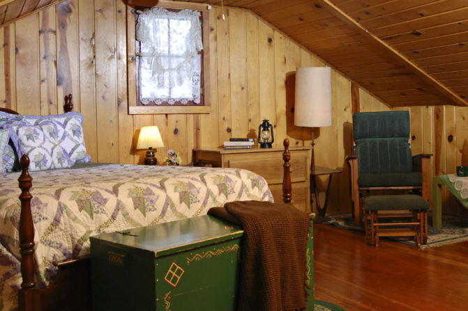 knotty pine wood panelled walls and pitched roofceiling with one window with lace window treatment, large 4 wood bed with cream, soft green and purple quilt, antique green chest with brown throw blanket in front and green and wood chair with ottaman