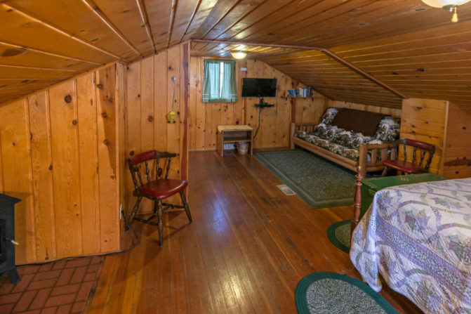 wide angle view of large knotty pine panelled wall and ceiling with bed in forground with cream, light green and purple quilt and window with green window treatment, wood futon couch on green rug and tv