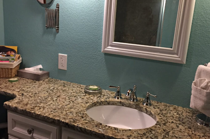 white single sink vanity with granite countertops, hair dryer, white framed mirror against seafoam green painted wall