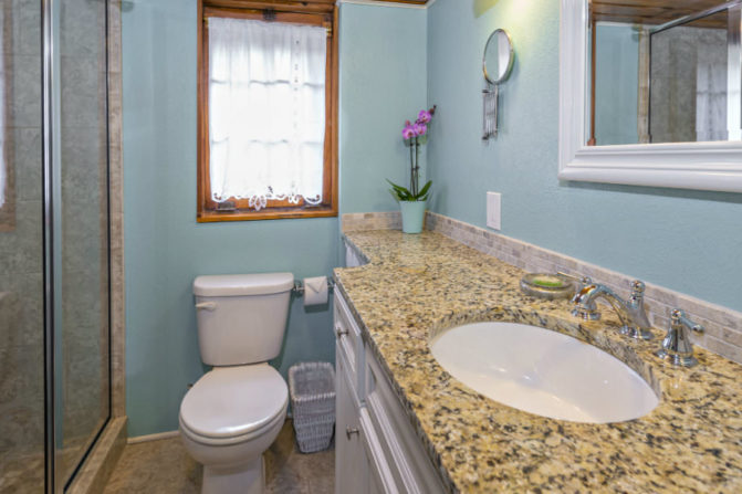 white single sink vanity with granite countertops,, white framed mirror against seafoam green painted wall, walk in shower with glass enclosure and white commode, window with lace window treatment