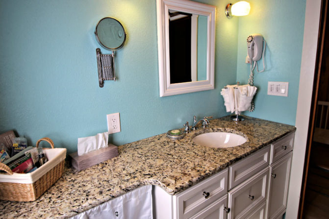 white single sink vanity with granite countertops, hair dryer, bath amenities, white framed mirror against seafoam green painted wall
