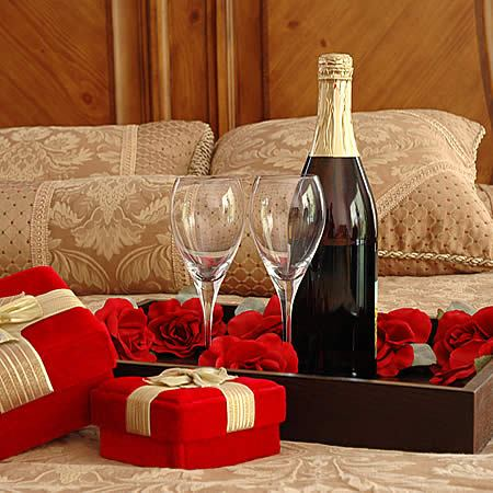 Bed topped with of red roses, wine bottle and two glasses and red velvet heart shaped box with gold ribbon