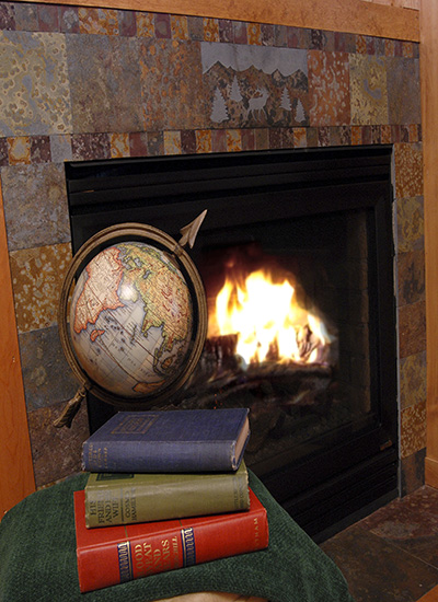 Fireplace with roaring fire, books and a globe