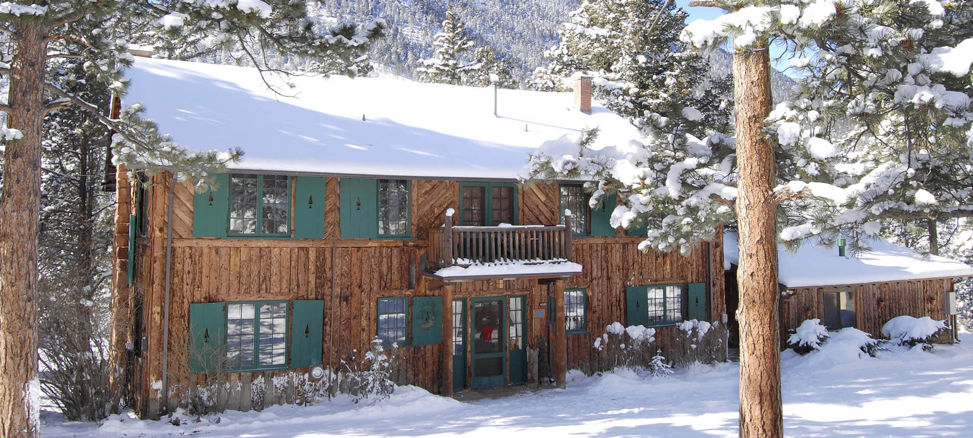 Brown wood cabin with green shutters and snow covered roof surrounded by snowcapped pine trees and snow covered ground