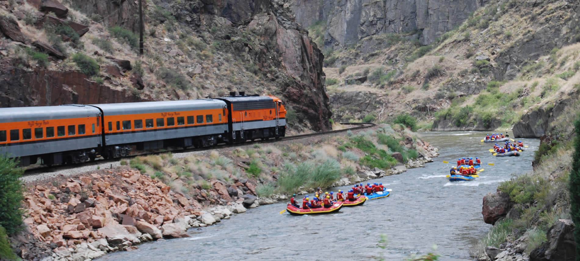 White water rafts floating down a river surrounded by steep rocky mountains and an orange train going by