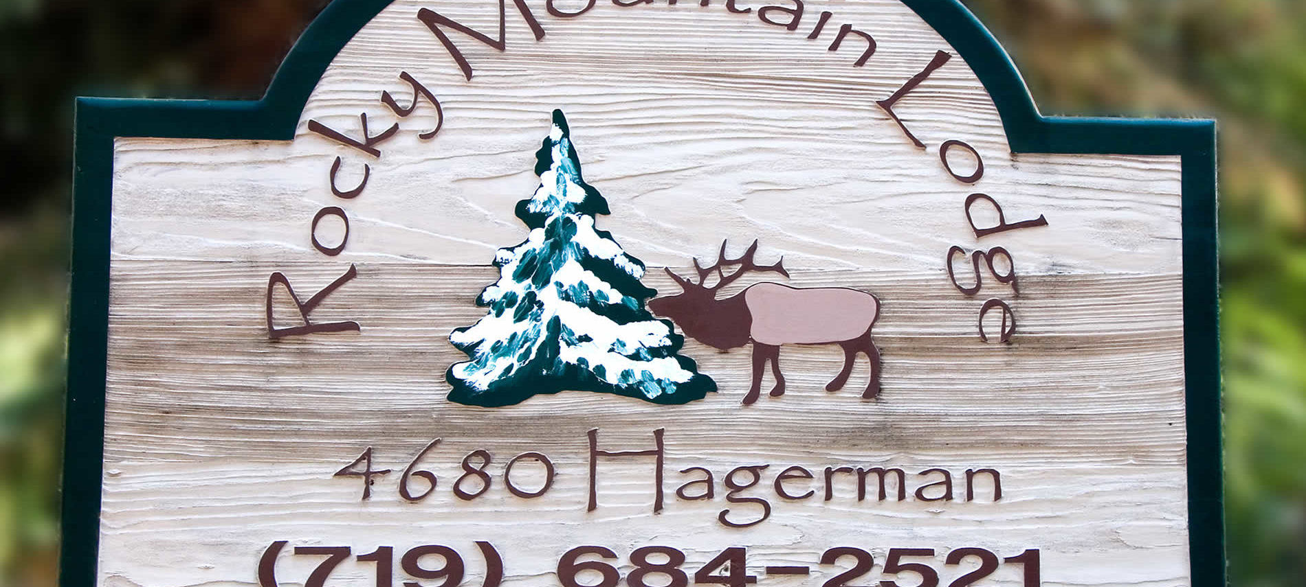 Wood sign trimmed in green that says Rocky Mountain Lodge, 4680 Hagerman, (719) 684-2521 in brown lettering