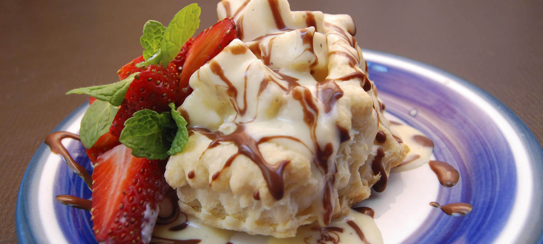 White and blue plate topped with delicious dessert drizzled with brown and white sauce and red strawberries