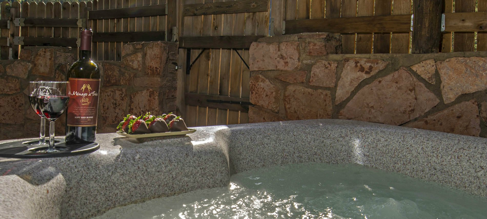 Hot tub in private space with wood fence and champagne on the side.