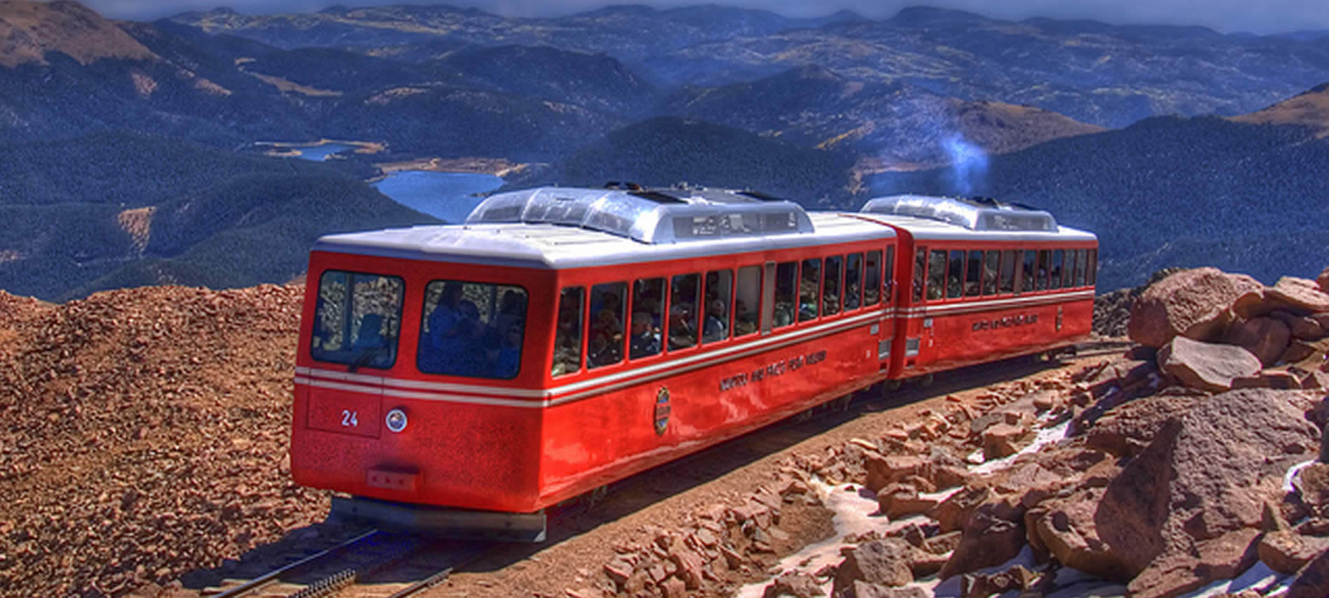 Bright red train going down a steep mountain surrounded by rocky and tree covered mountains