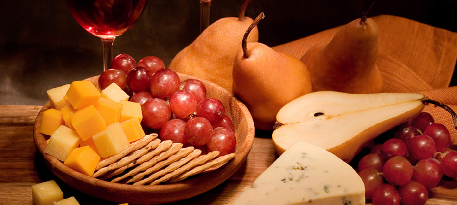 Table topped with sliced pears, aged cheese, red grapes, and a wooden bowl of crackers, cheese and grapes