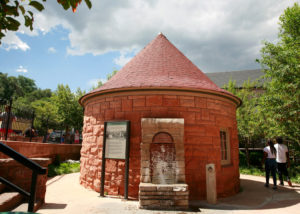 Red Clay building with cone shaped roof and water running from a fountain.