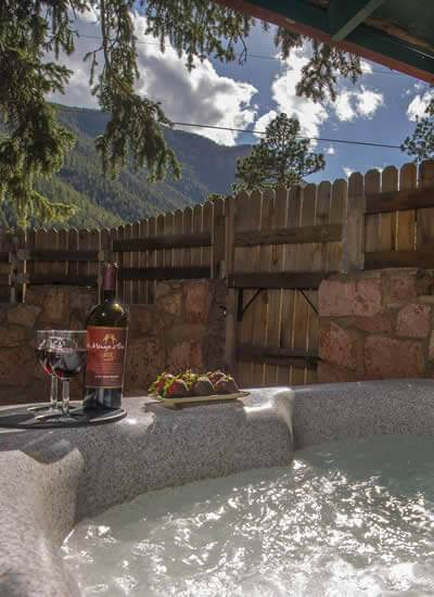 Bottle of red wine, two glasses, and chocolate covered strawberries on edge of hot tub overlooking mountains and blue skies