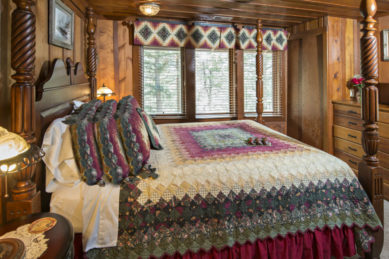 wood panelled room with four poster bed and soft green maroon and pink quilt with large triple window in forground with matching valance and wood chest of drawers with tv on top