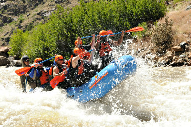 Blue raft filled with 7 people in red life vests and oars floating through white water river rapids