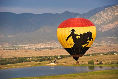 red, yellow and black hot air baloon with image of cowboy on a horse over a lake and mountains in the background